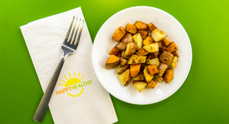 A plate of cubed and roasted potatoes with a HappyHealthy napkin and fork to the side.