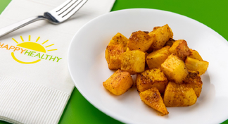 Roasted Turnips on white plate next to white HappyHealthy napkin and fork