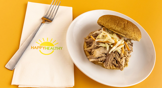 Slow Cooker Pulled Pork on a bun, plated on a white plate next to a HappyHealthy napkin and fork
