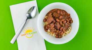 Slow Cooker Red Beans and Rice in a bowl with a spoon on a HappyHealthy napkin.