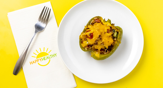 A stuffed bell pepper on a white plate next to a Happy Healthy Napkin and Fork