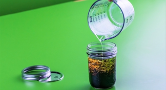 Oil pouring into glass jar