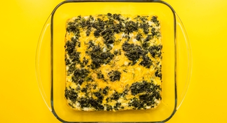 Egg and spinach casserole baked in a clear baking dish.