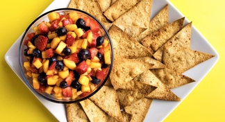 plate with bowl of fruit salsa and tortilla chips