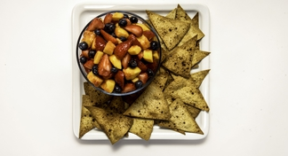 plate with tortilla chips and bowl of salsa