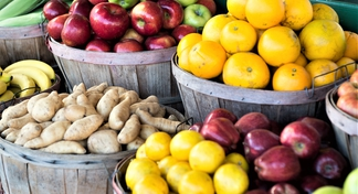 Variety of fruits and vegetables in baskets at farmers market (red apples, green apples, sweet potatoes)