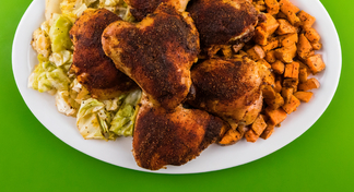 Blackened chicken, roasted cabbage, and roasted sweet potatoes on white plate with green background.
