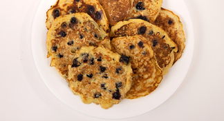 A white plate of blueberry oatmeal pancakes