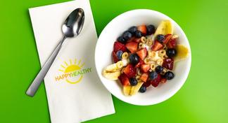 Breakfast Banana Split in white bowl next to HappyHealthy napkin and spoon.