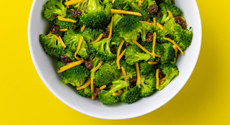 Broccoli salad in white bowl with yellow background.