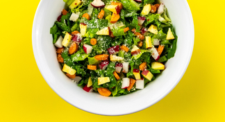 Chopped salad in white bowl with yellow background.