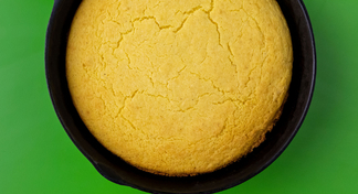 A frying pan of baked cornbread on a green background
