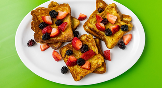 3 stacks of French toast topped with blackberries and raspberries on a white plate