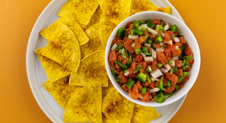 Homemade Tomato Salsa in white bowl on white plate with tortilla chips