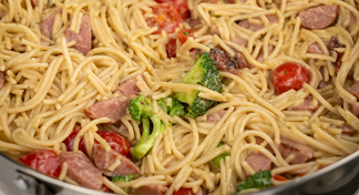 A bowl of pasta with broccoli, ham and tomatoes