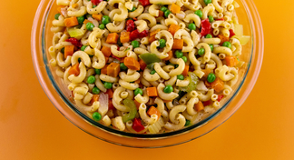 Macaroni Salad in clear bowl with orange background.