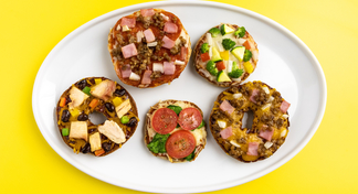 Five different mini pizzas on a white plate