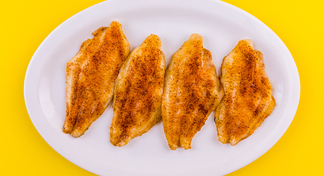 Four fillets of Oven Blackened Catfish on white oval-shaped plate