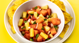 A white bowl of watermelon salsa on a white plate of tortilla chips