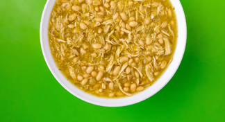White Chicken Chili in white bowl with green background.