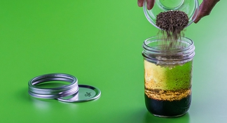 Hand pouring contents of bowl into a jar to make salad dressing