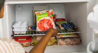 Woman placing bag of frozen fruit in freezer.