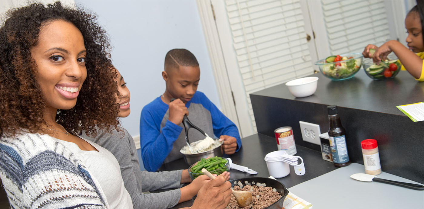 A family prepares a healthy dinner, green salad, green beans, ground beef and mashed potatoes, together.