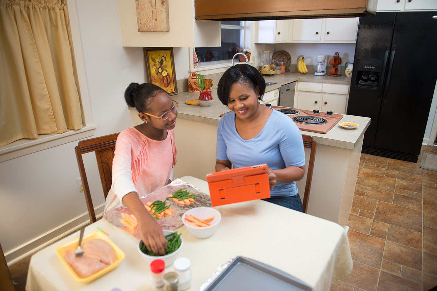 While looking at a tablet, a woman and girl prepare foil packs of chicken, green beans, and carrots.