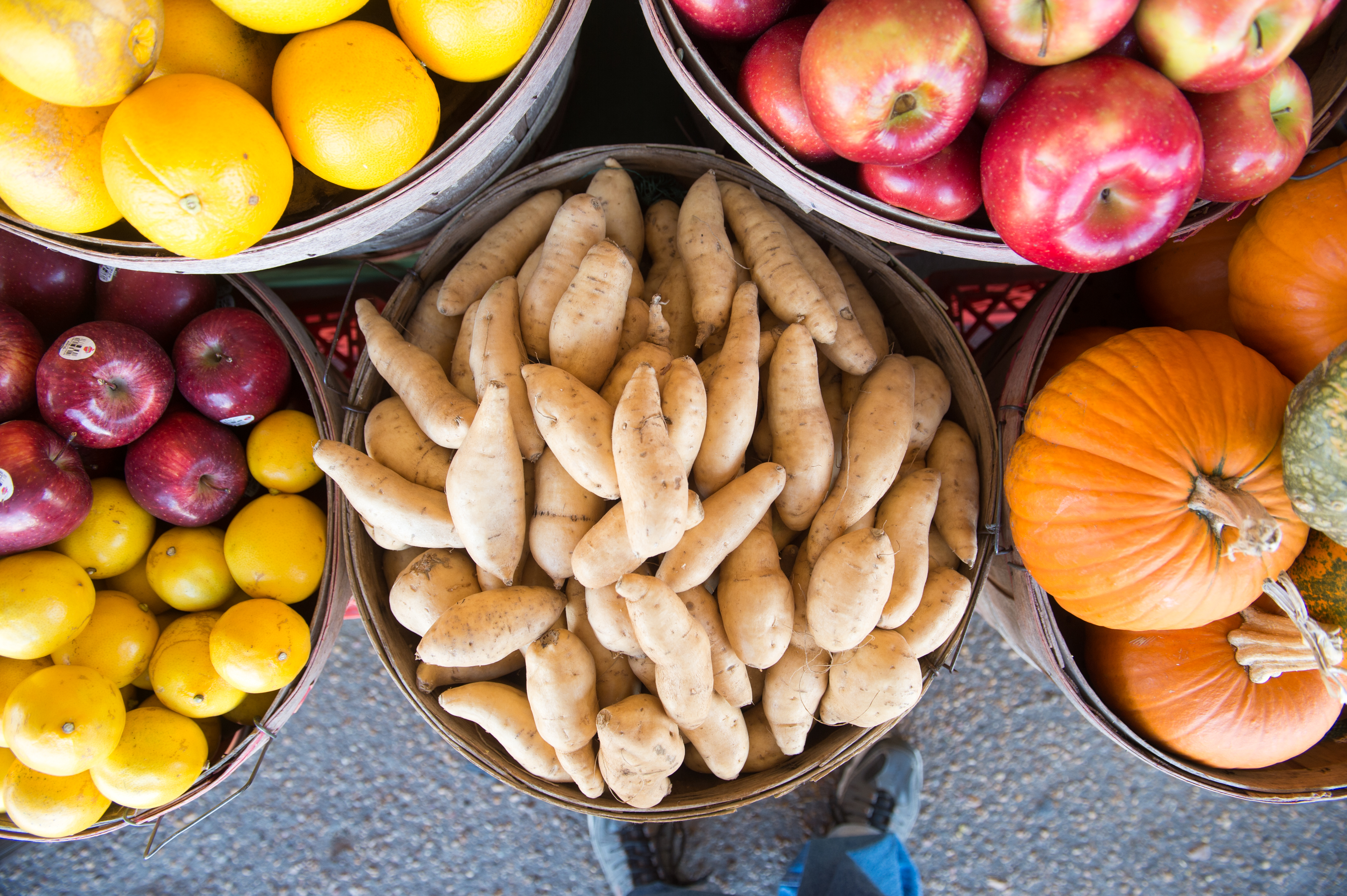 Potatoes, pumpkins, apples, and other produce arranged in buckets at a farmers market.